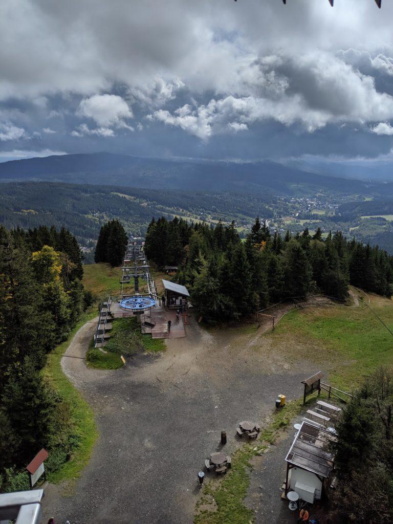 Fotka horní stanice lanovky na Špičáku s pohledem do údolí
