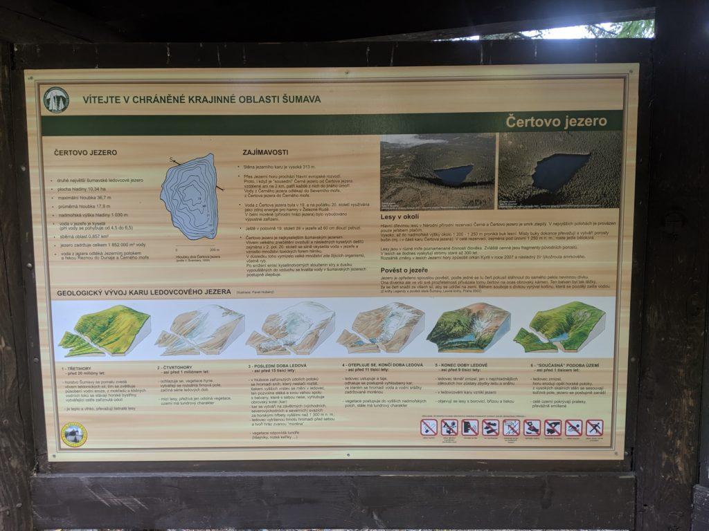 Informační tabuli o Čertovo jezeře popisující jeho vznik a vlastnosti.